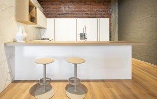 Cocina Copatlife en termoestructurado blanco neve y madera rovere spazolato, con taburetes Hula de Andreu World.